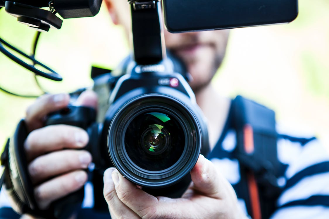Person Holding Canon Dslr Camera Close-up Photo
